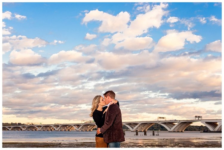 Engagement session in Old Town Alexandria on the water with gorgeous clouds and bridge in background